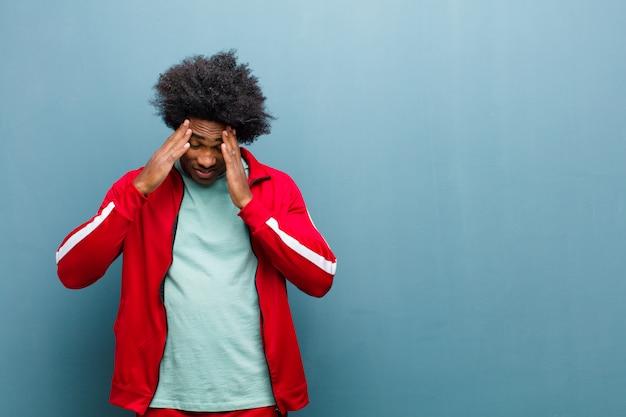 Uomo di sport nero giovane che sembra stressato e frustrato, lavorando sotto pressione con un mal di testa e turbato con problemi contro la parete del grunge
