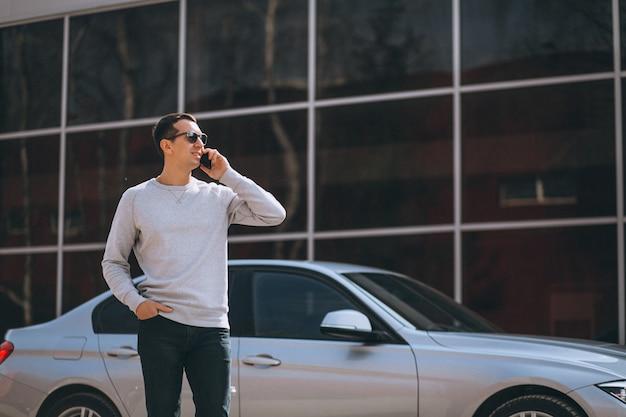 Uomo di successo bello in macchina con il cellulare