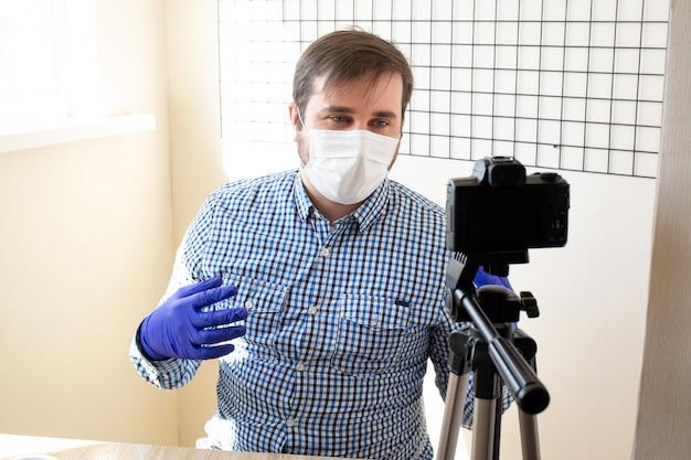 Uomo di successo che registra video, utilizzando la fotocamera digitale in ufficio oa casa, coronavirus, malattia, infezione, quarantena, mascherina medica