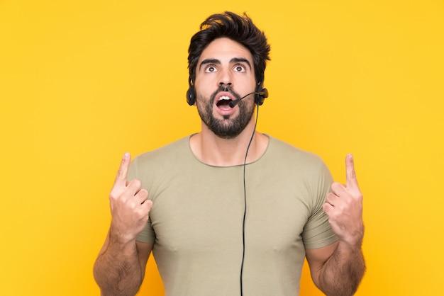 Uomo di telemarketer che lavora con un auricolare sul muro giallo isolato che punta con il dito indice una grande idea