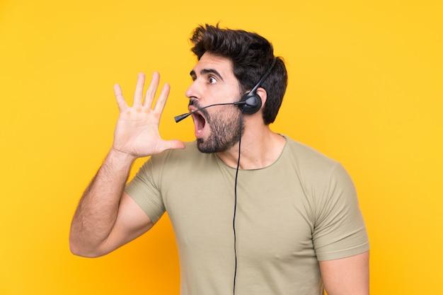 Uomo di telemarketer che lavora con una cuffia avricolare sopra la parete gialla isolata che grida con la bocca spalancata