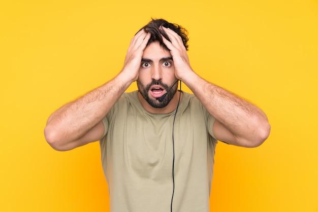 Uomo di telemarketer che lavora con una cuffia avricolare sopra la parete gialla isolata con espressione facciale di sorpresa