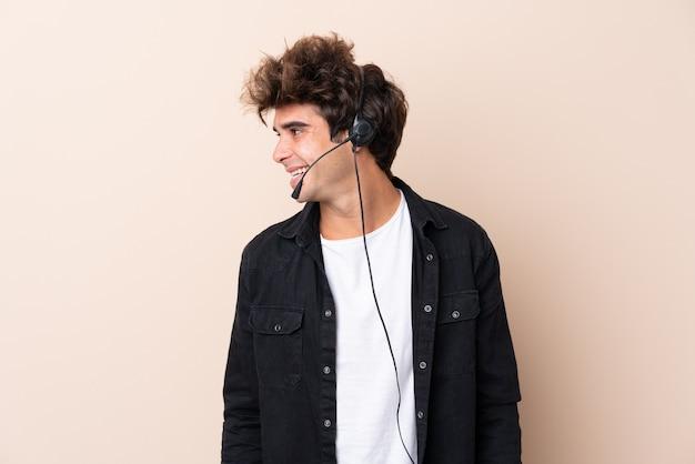 Uomo di telemarketer che lavora con una cuffia avricolare sopra la parete isolata che osserva al lato