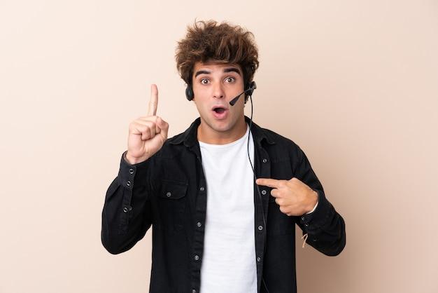 Uomo di telemarketer che lavora con una cuffia avricolare sopra la parete isolata con espressione facciale di sorpresa