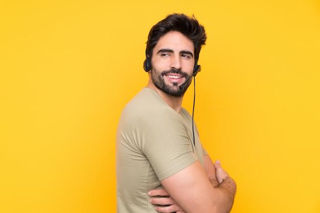 Uomo di telemarketer che lavora con una cuffia avricolare sopra la risata gialla isolata della parete