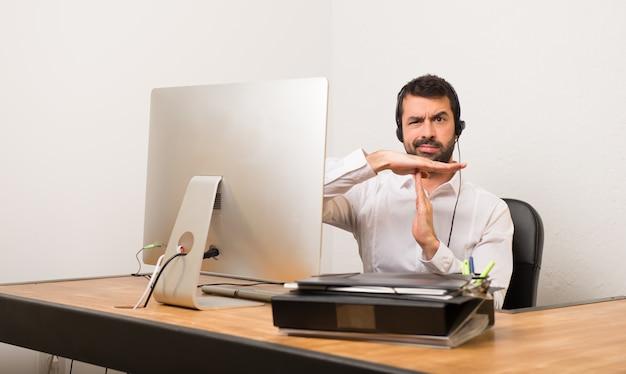 Uomo di telemarketer in un ufficio che fa il gesto di arresto con la sua mano per fermare un atto