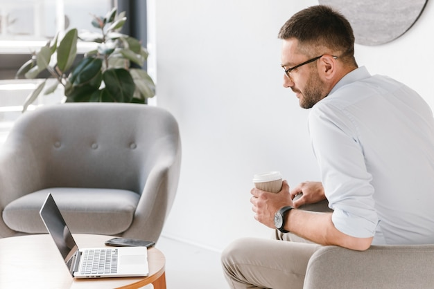 Uomo di ufficio adulto 30s in camicia bianca seduto in poltrona e bere caffè da asporto, mentre guarda lo schermo del laptop in interni di affari