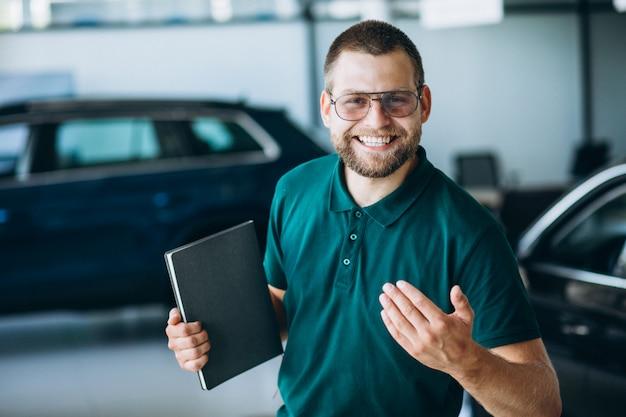 Uomo di vendite in un autosalone che vende un'auto