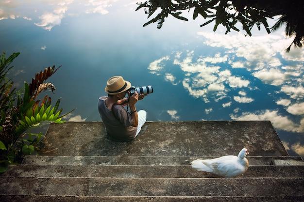 Uomo di viaggio che prende una fotografia al vecchio pilastro contro la bella riflessione del cielo blu sul fondo dell'acqua