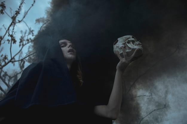Uomo di vista bassa che tiene un cranio in nebbia nera