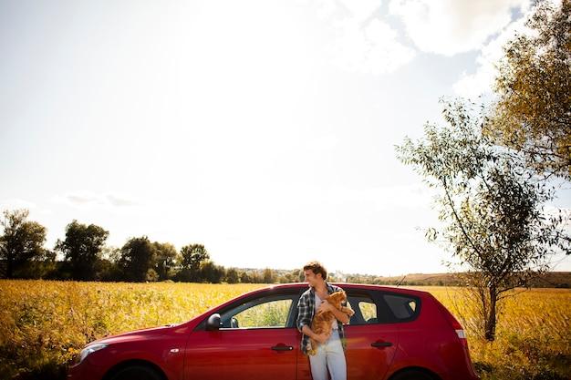 Uomo di vista della fronda che tiene un gatto davanti ad un'automobile