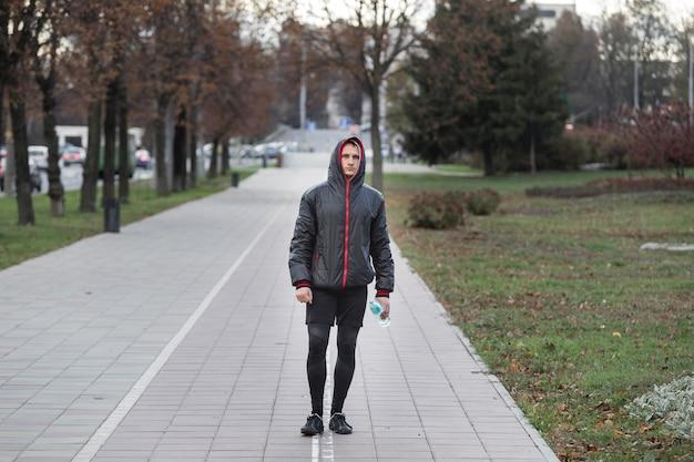 Uomo di vista frontale che cammina e che tiene una bottiglia di acqua