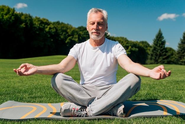 Uomo di vista frontale che medita in natura