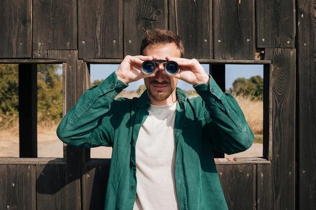 Uomo di vista frontale che osserva tramite il binocolo