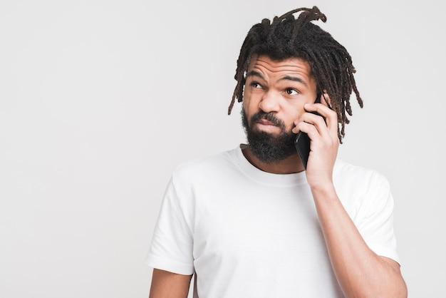 Uomo di vista frontale che parla sul suo smartphone