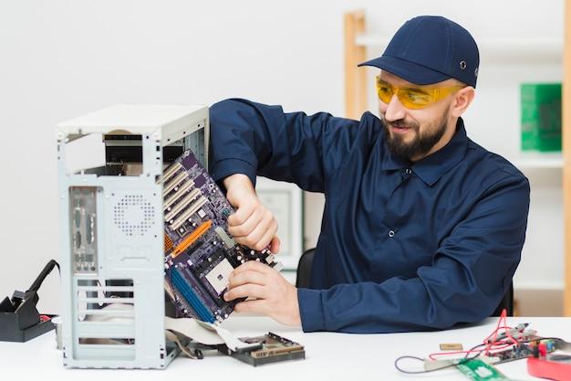 Uomo di vista frontale che ripara un computer