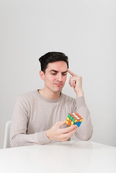 Uomo di vista frontale che risolve i cubi di rubik