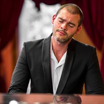 Uomo di vista frontale che sente il pianoforte classico