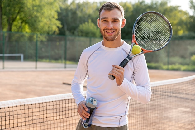 Uomo di vista frontale che si idrata sul campo da tennis