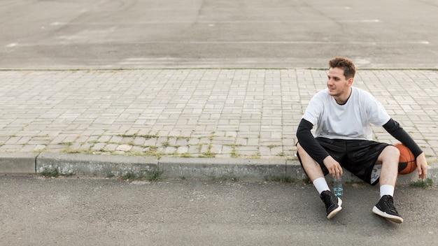 Uomo di vista frontale che si siede con una pallacanestro