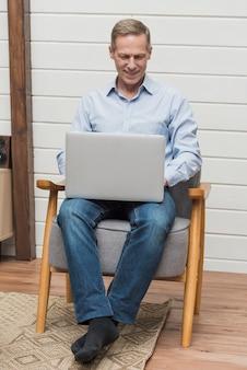 Uomo di vista frontale che si siede su una sedia mentre guardando su un computer portatile