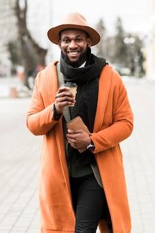 Uomo di vista frontale in cappotto arancio che tiene una tazza di caffè all'aperto