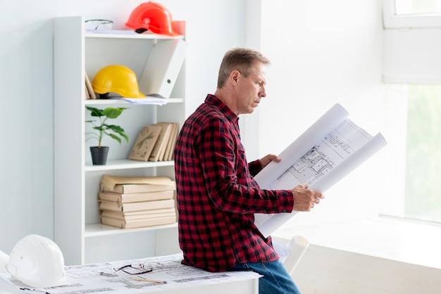 Uomo di vista laterale che controlla progetto architettonico