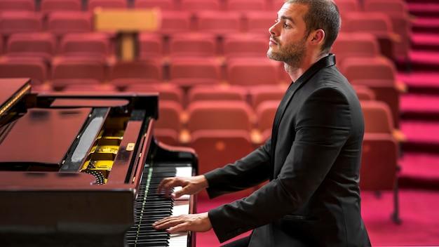 Uomo di vista laterale che gioca il concerto di pianoforte classico