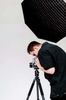 Uomo di vista laterale che indossa i vestiti neri che lavorano nello studio