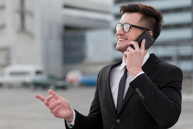 Uomo di vista laterale che parla sopra il telefono
