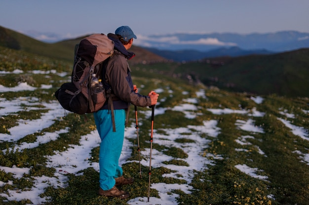Uomo di vista laterale che sta sul campo con i resti di neve con l'escursione zaino e bastoni