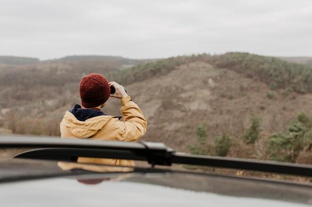 Uomo di vista posteriore che osserva tramite il binocolo