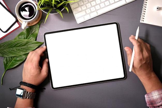 Uomo di vista superiore che tiene la compressa dello schermo in bianco sullo scrittorio domestico dell'area di lavoro