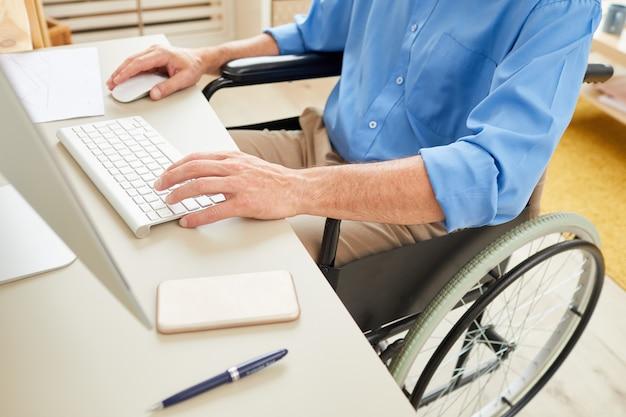 Uomo disabile che scrive sul computer