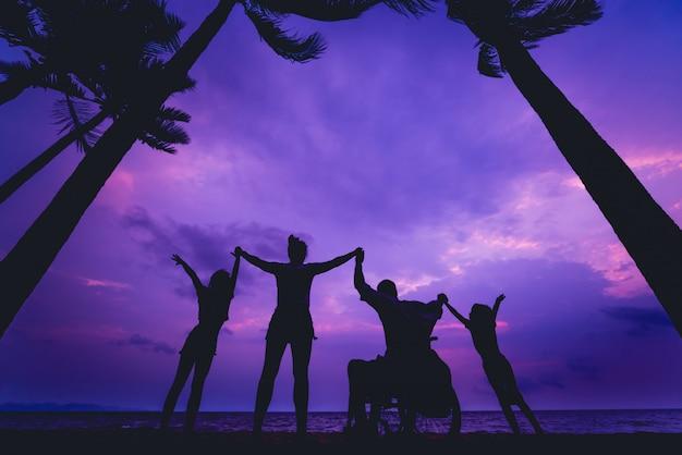 Uomo disabile in sedia a rotelle con la sua famiglia sulla spiaggia. sagome al tramonto