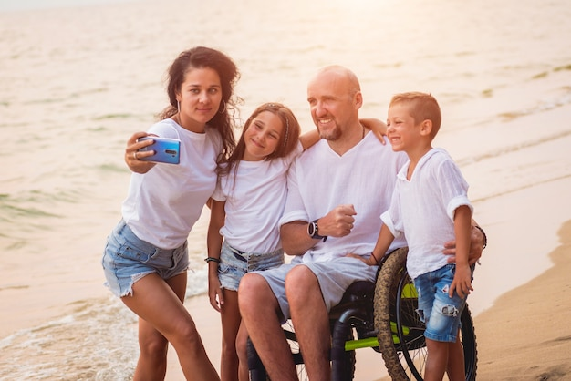 Uomo disabile in sedia a rotelle con la sua famiglia sulla spiaggia.