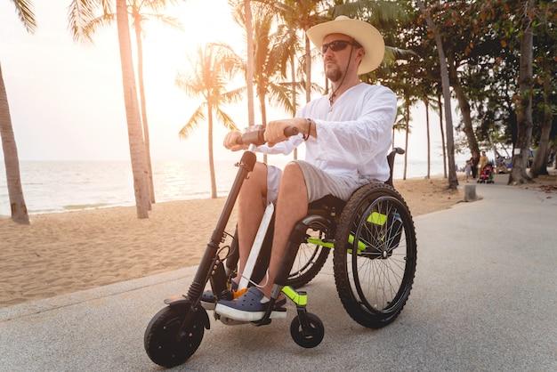 Uomo disabile in sedia a rotelle con scooter elettrico sulla spiaggia