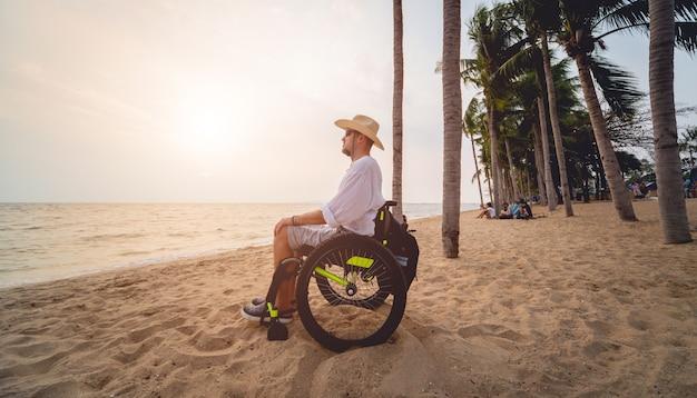 Uomo disabile in sedia a rotelle sulla spiaggia.