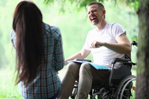 Uomo disabile maschio con l'amica che sorride sul ritratto della passeggiata del parco
