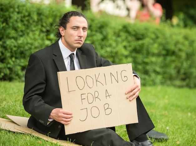 Uomo disoccupato frustrato con il segno che si siede al prato inglese.