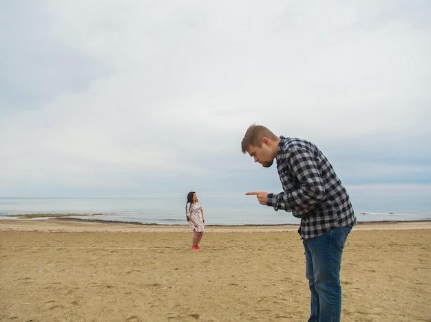 Uomo dispiaciuto che rimprovera sua moglie sulla spiaggia. problemi di conflitto, litigi e relazioni.