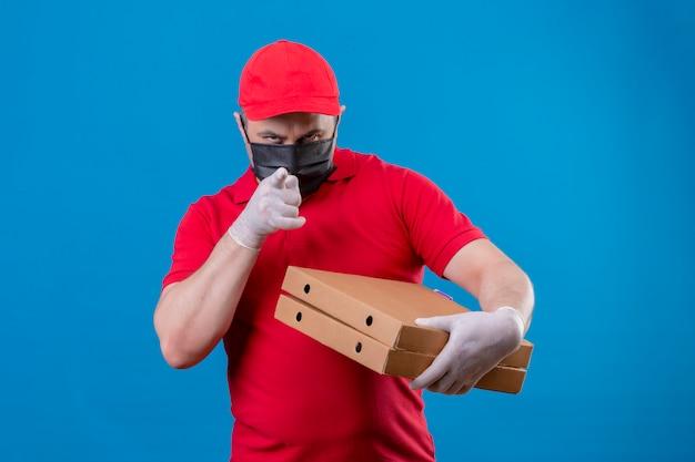 Uomo dispiaciuto consegna indossando l'uniforme rossa e cappuccio in maschera protettiva facciale tenendo scatole per pizza che puntava il dito con la faccia accigliata sul backgrou blu