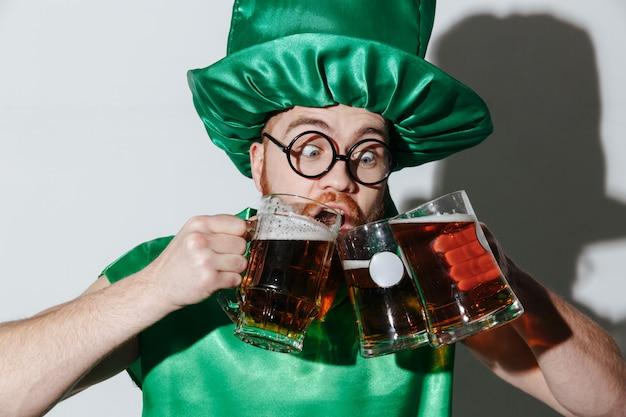 Uomo divertente che beve dalle molte tazze