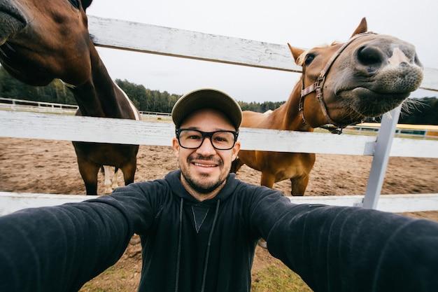Uomo divertente che prende selgie con due cavalli dietro lui.