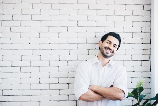 Uomo divertente che sorride accanto ad un muro di mattoni