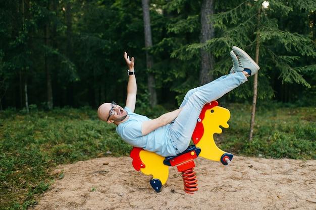 Uomo divertente emozionante in vestiti blu alla moda che monta il cavallo del giocattolo al campo da giuoco dei bambini nella foresta con il fronte espressivo