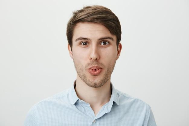 Uomo divertente giocoso arriccia la lingua e sorridente