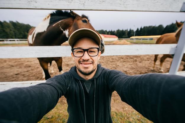 Uomo divertente in occhiali prendendo selfie con i cavalli dietro di lui.