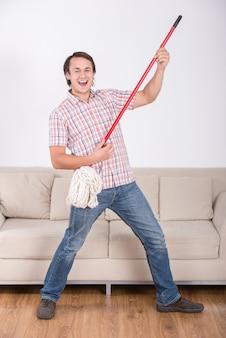 Uomo divertente sta rastrellando il pavimento e suonando musica usando la scopa.