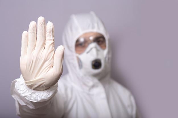 Uomo, dottore in tuta protettiva, con maschera, occhiali e guanti contro l'infezione, il covid 19, durante la pandemia, si ferma con la mano, si ferma, resta a casa.